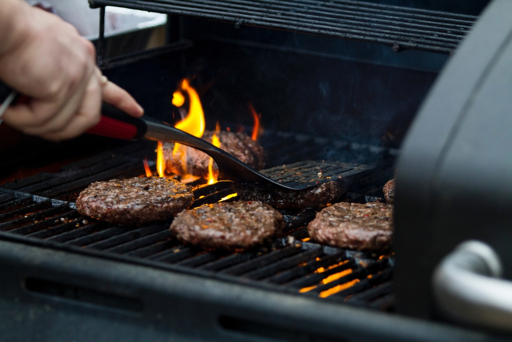 Burgers cooking on a grill.